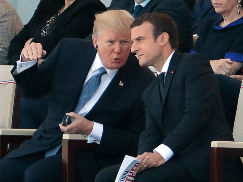 French President Emmanuel Macron (R) listens to US President Donald Trump as they attend the annual Bastille Day military parade on the Champs-Elysees avenue in Paris on July 14, 2017. The parade on Paris's Champs-Elysees will commemorate the centenary of the US entering WWI and will feature horses, helicopters, planes and troops. / AFP PHOTO / joel SAGET